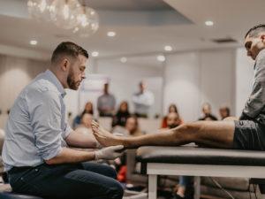Podiatrist diagnosing foot of patient